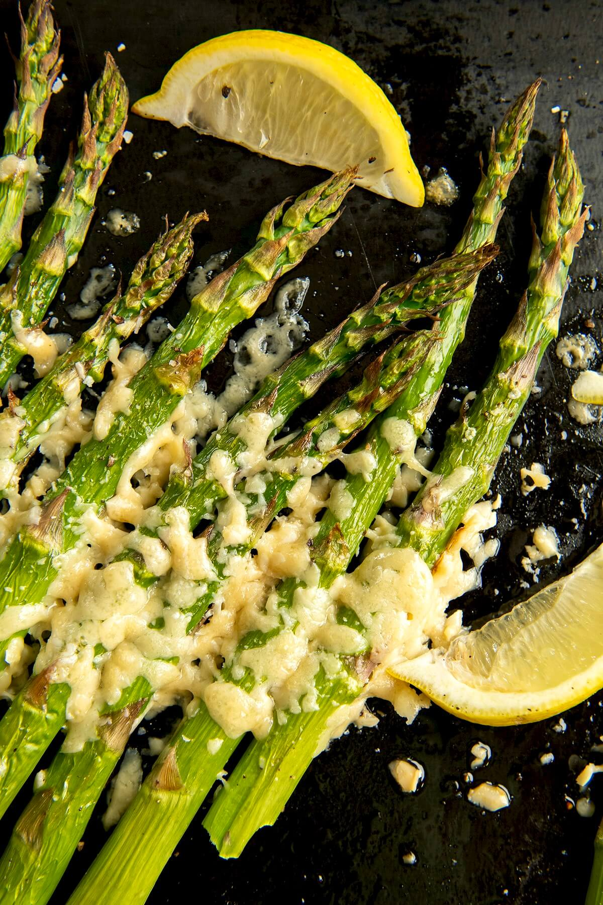 Asiago cheese provides a delightful alternative to Parmesan, adding a unique twist to simply roasted asparagus. The flavor of this side dishes belies its ease. Lemon slices make a pretty garnish.