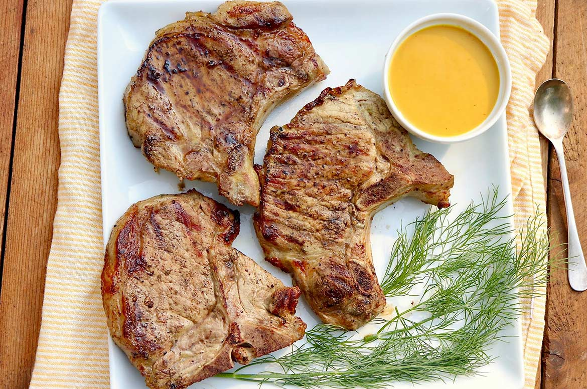 """Hold onto that leftover pickle juice! Crazy as it may seem, the components are that of a basic brine, and it will tenderize and flavor pork chops and chicken with no """"pickle-y"""" taste. A sunshiny sauce adds an extra dimension of flavor with minimal effort."""