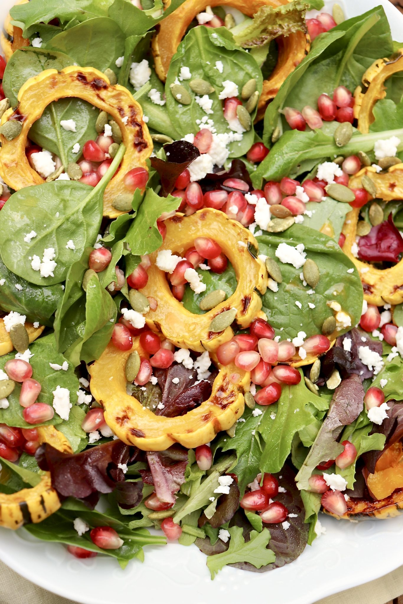 Radiant jewel tones make this Roasted Delicata Squash & Pomegranate Salad as stunning as it is healthy. It offers an eye catching and refreshingly light element on a holiday table and can be paired with a protein of choice for a well rounded meal any night. Feel free to swap in another winter squash of choice or use dried cranberries in place of pomegranate!