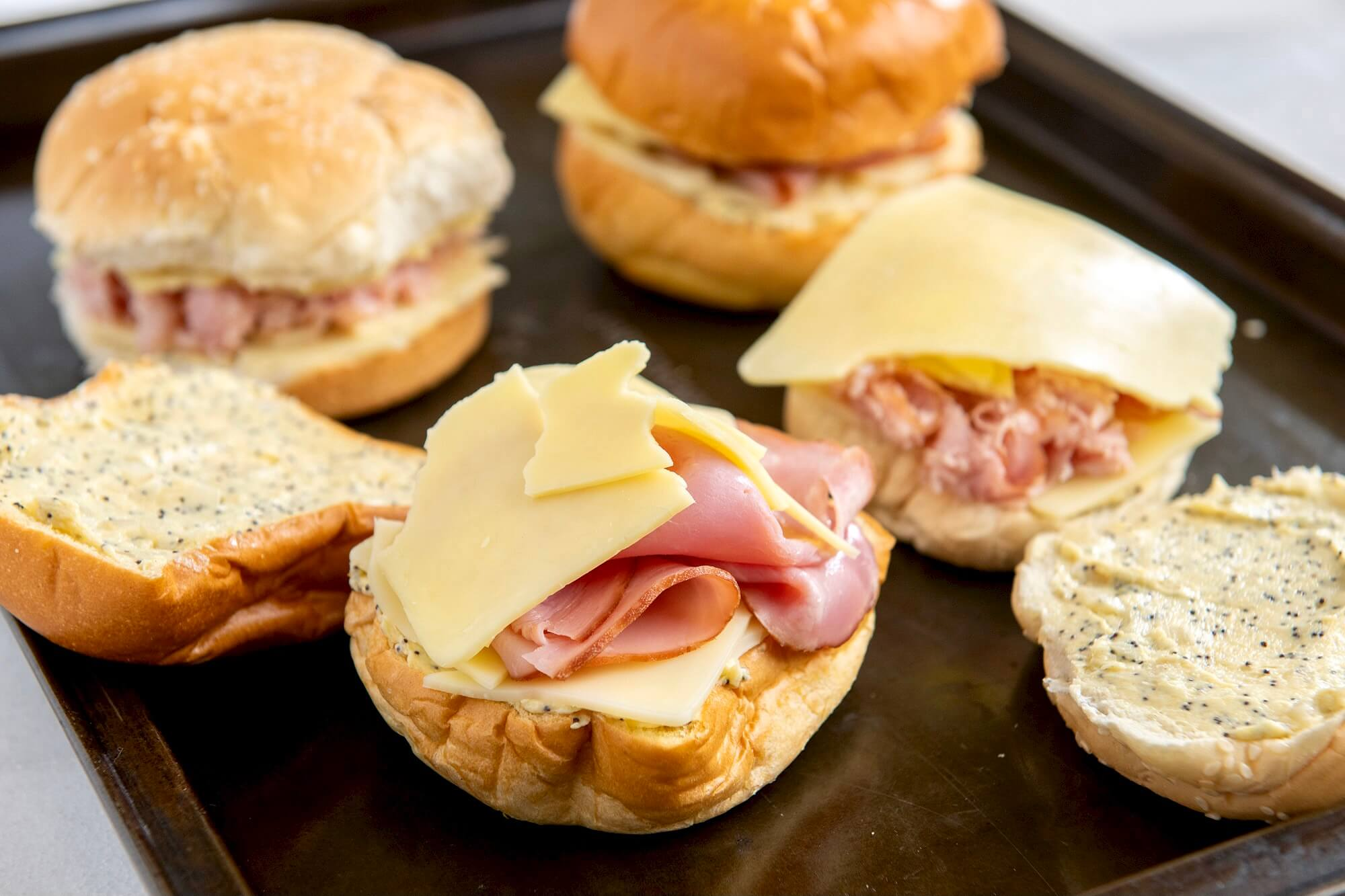 The classic ham sandwich is redefined with two kinds of cheese, a flavorful spread, and a quick trip to the oven. These toasty bunwiches are easy to make-ahead and as well suited to casual entertaining as they are to a quick weeknight meal with a side of soup!